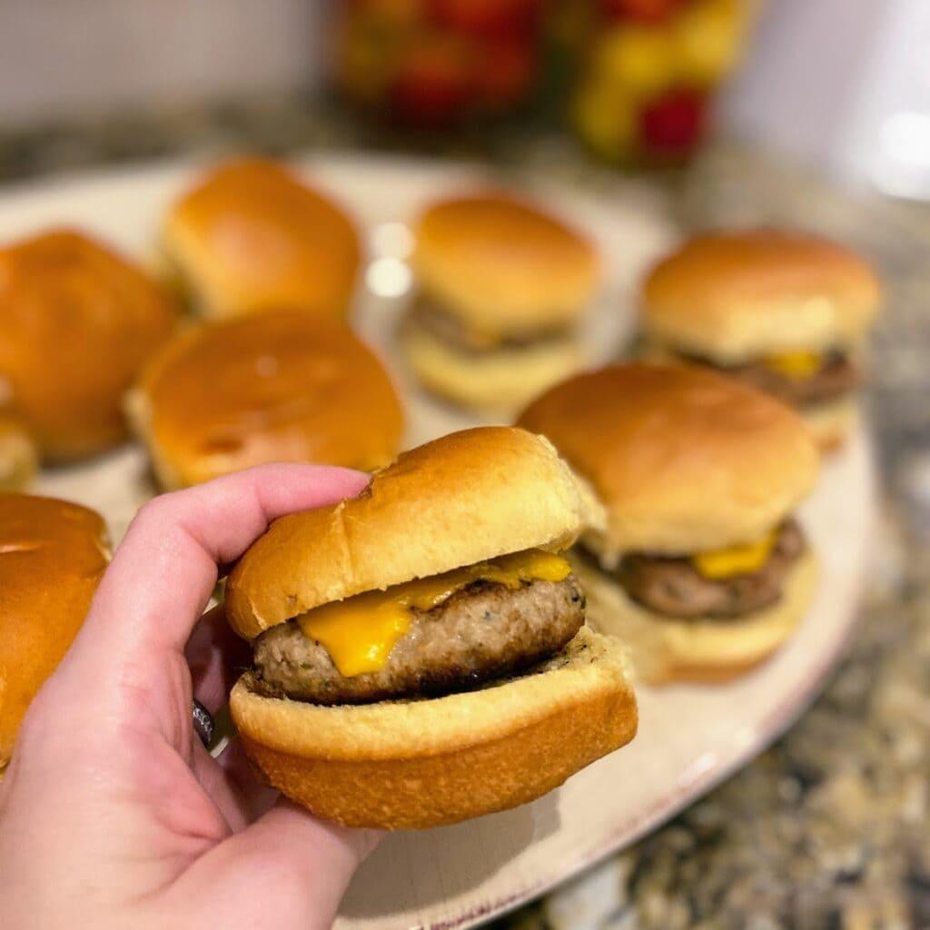 hand holding turkey burger slider with cheese