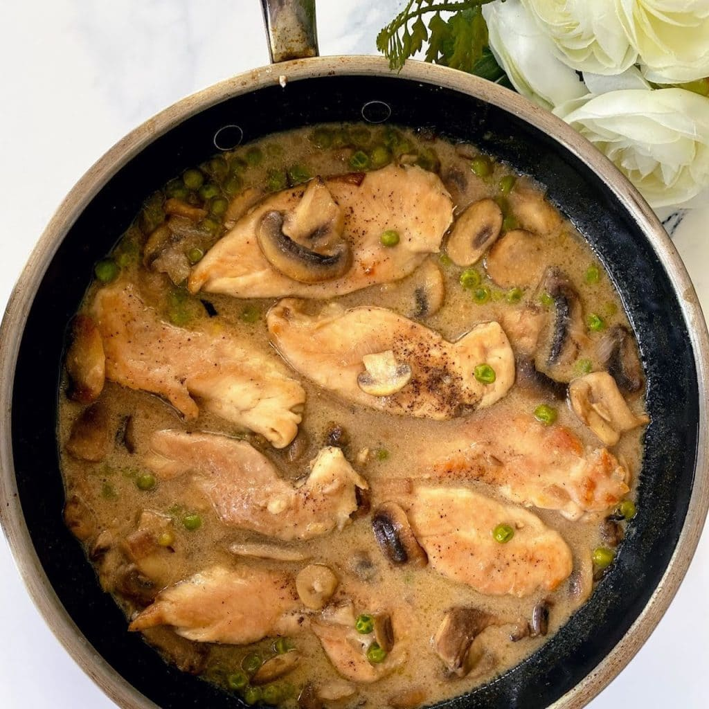 Chicken marsala with peas in pan