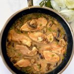 Marsala chicken with mushrooms and peas in pan