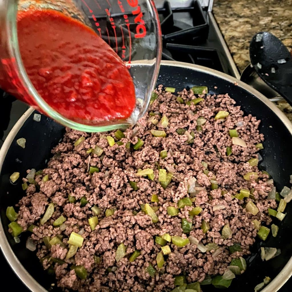 adding chili sauce to meat and veggie mixture for old fashioned sloppy joes recipe