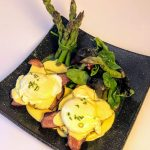 eggs benedict with bacon and hollandaise sauce on dark plate with bunch of asparagus and side of greens