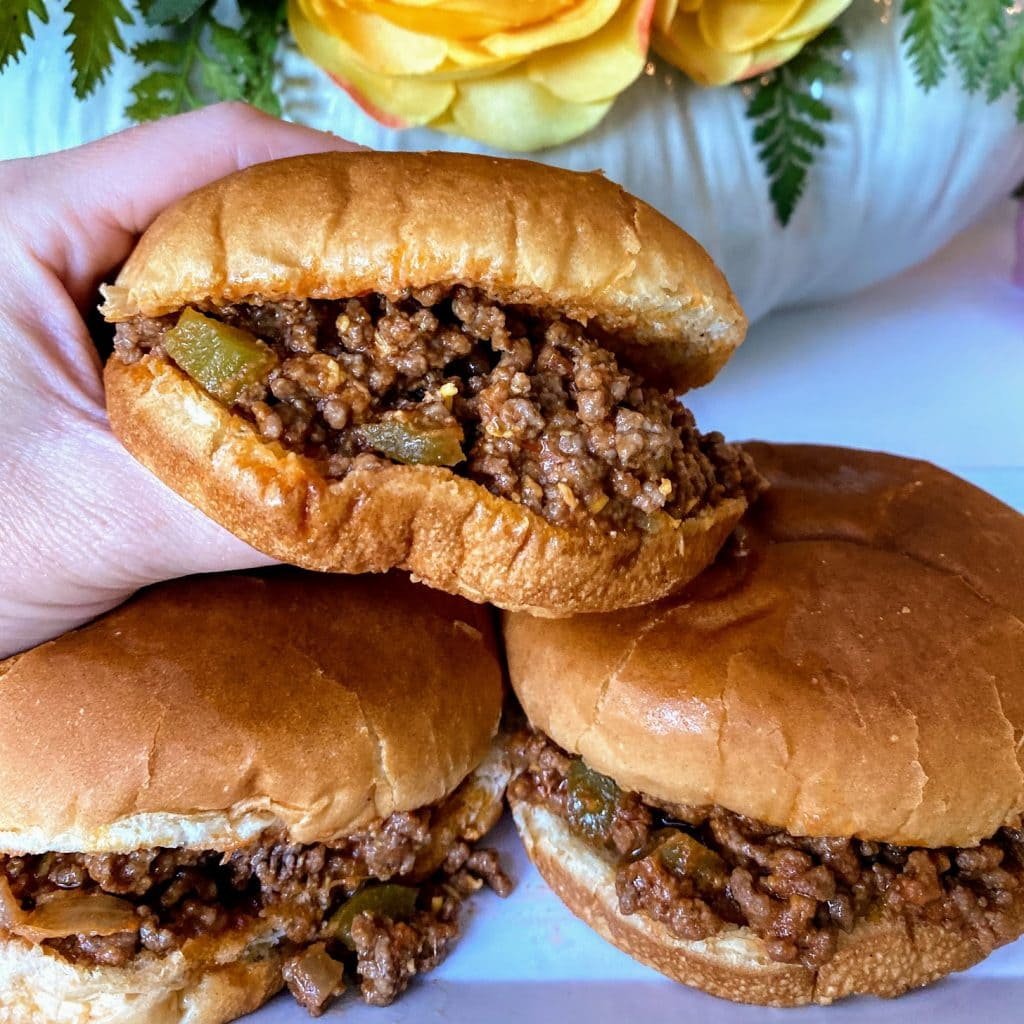 hand holding sloppy joes and two sandwiches resting on a plate