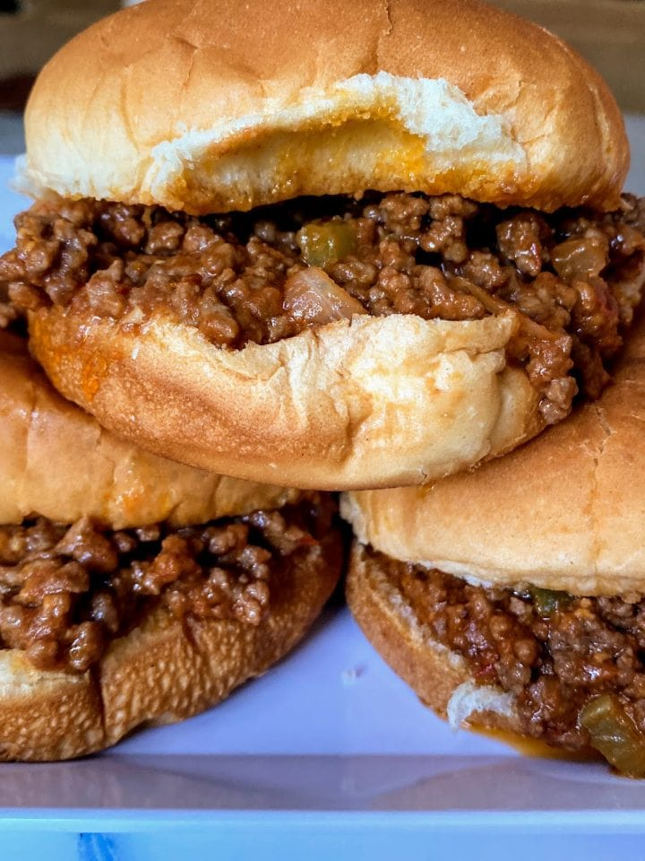 three sloppy joes with meat spilling out