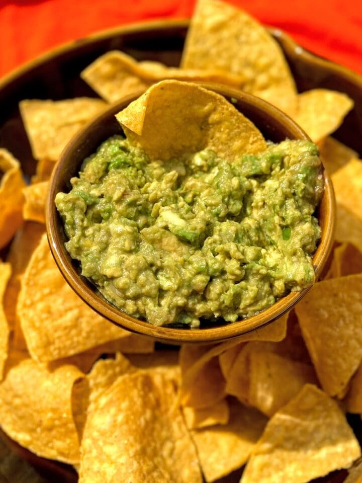 bowl of guacamole and tortilla chips on orange tablecloth