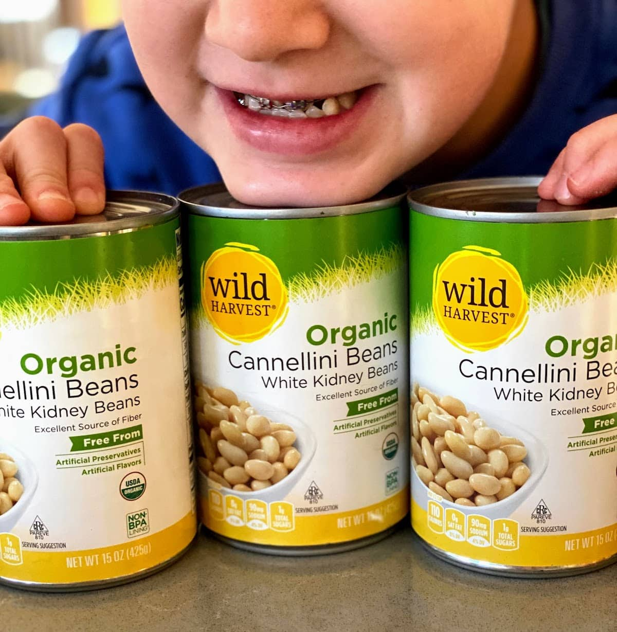 child holding three cans of cannellini white kidney beans